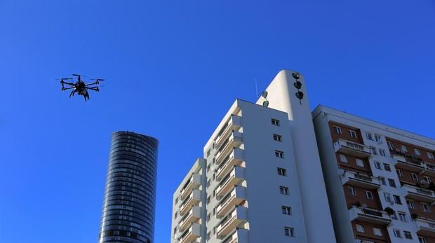 Imagen de un dron surcando el cielo junto a unos edificios