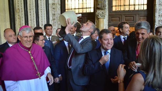 El arzobispo de Toledo sontríe en el claustro de la catredral junto a Page y Tolón mientras Gutiérez bebe del botijo