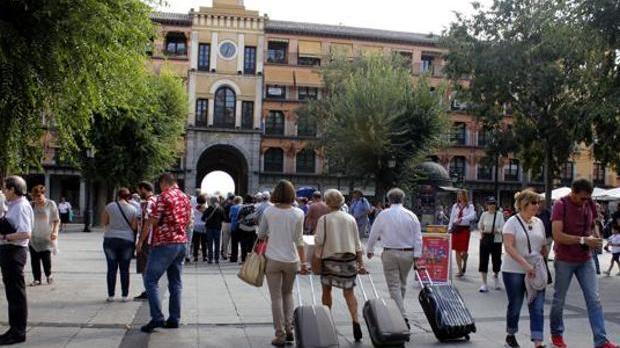 Imagen de turistas con sus maletas por la plaza de Zocodover de Toledo