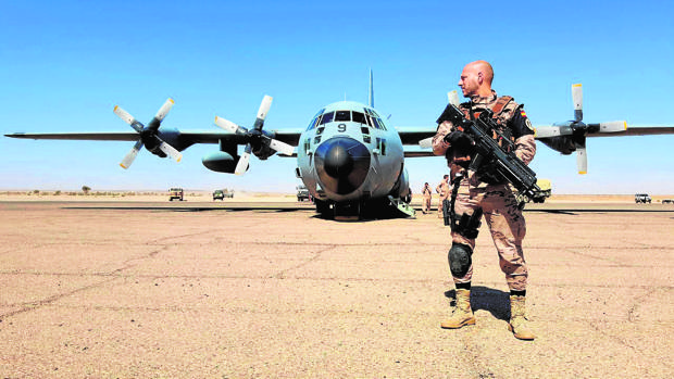 Un militar vigila el perímetro donde acaba de aterrizar un avión C-130