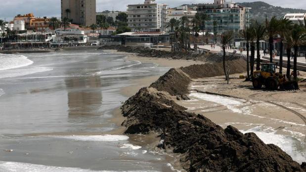 Muro de arena para contención del agua por el temporal en la playa de Jávea (Alicante)