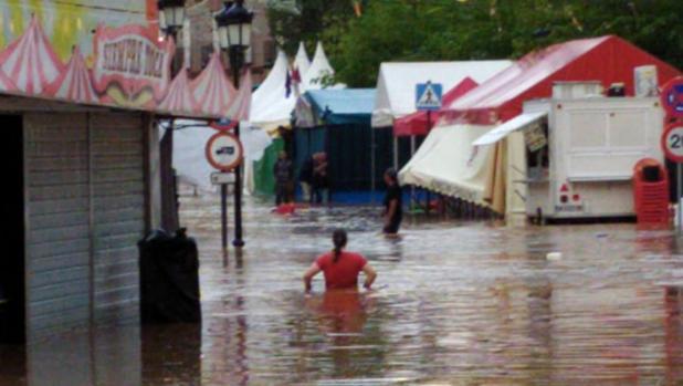 Una mujer camina por la zona inundada donde estaban las atracciones de feria