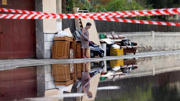 Una afectada por las inundaciones en Dolores (Alicante) junto a enseres en la puerta de su domicilio
