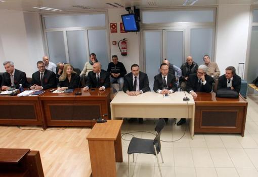Los siete acusados del crimen (al fondo), detrás de sus abogados defensores, este lunes en el juicio en Alicante