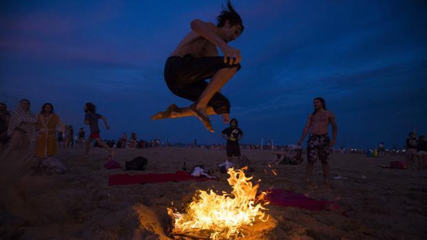 在巴伦西亚圣胡安之夜跳篝火的年轻人的档案图片