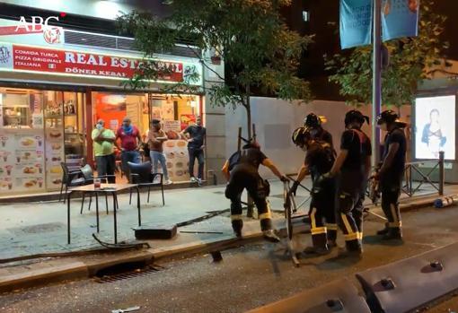 Los bomberos retiran los restos de valla arrancada por el taxi en el accidente