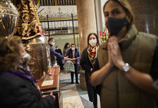 Varios fieles rezan ante la talla de Jesús de Medinaceli