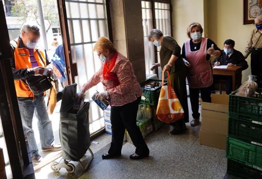 Varias mujeres mayores recogen productos básicos en el convento de capuchinos