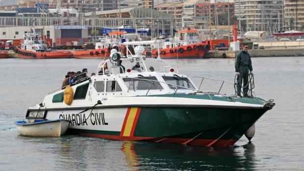 Una patrullera de la Guardia Civil remolca una patera en Alicante