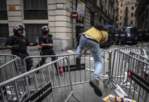 Un independentista vuelve a la manifestación tras hacerse el gallito por unos segundos saltando la valla de protección de la Comisaría de la Policía Nacional / ADRIÁN QUIROGA