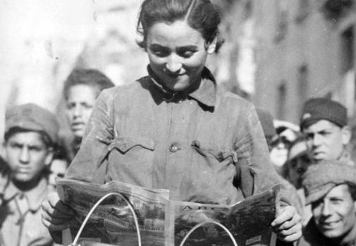 """Una miliciana del Batallón Ciclista """"Enrique Malatesta"""", leyendo las noticias de los frentes, en el diario ABC."""