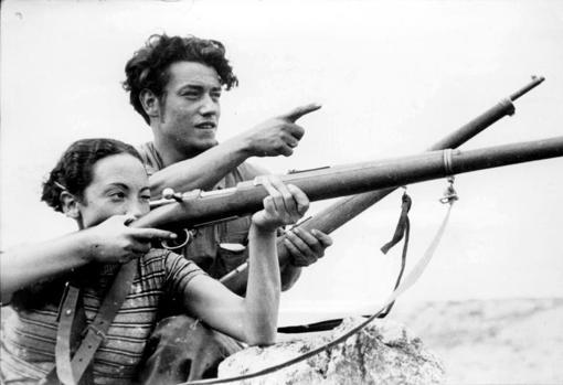 Un veterano de las milicias enseña a una miliciana el uso de un fusil