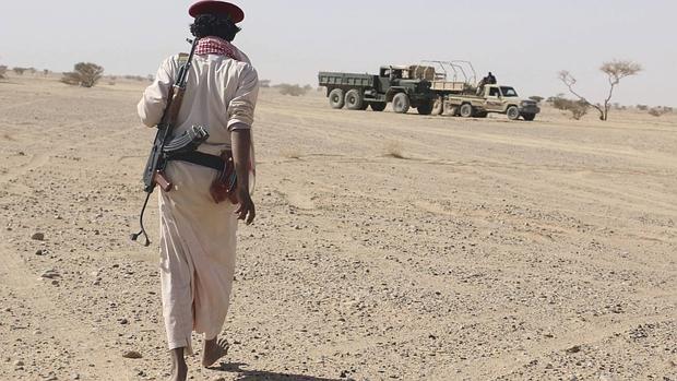 Un miembro de una milicia leal al gobierno depuesto se dirige hacia vehículos hutíes destruidos en una ofensiva
