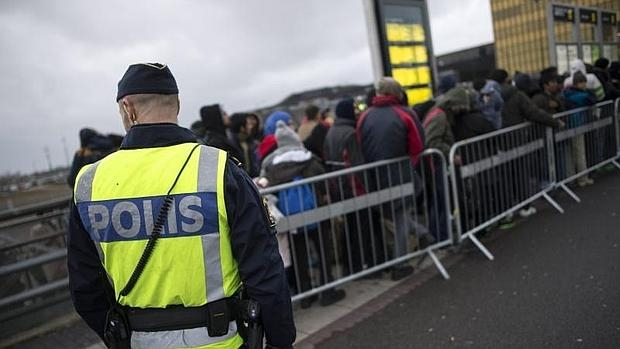Un policía vigila a un grupo de refugiados en Suecia