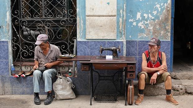 El congreso del partido no cambia la vida diaria de los cubanos. Unos habaneros reparan calzados o venden máquinas de coser en plena calle