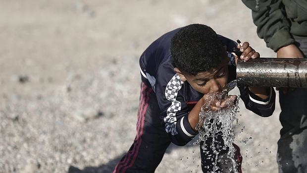 Un niño sirio refugiado en Idomeni bebe agua