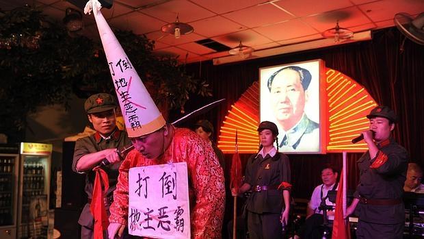 Representación teatral de la humillación y la ejecución de hombre durante la Revolución Cultural en un restaurante de china