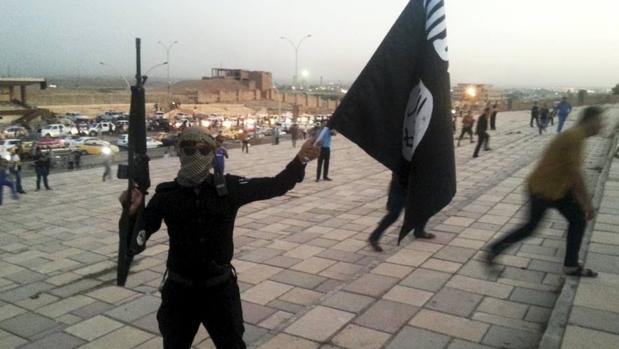 Un miembro de Daesh sostiene un arma y una bandera del grupo terrorista en Mosul
