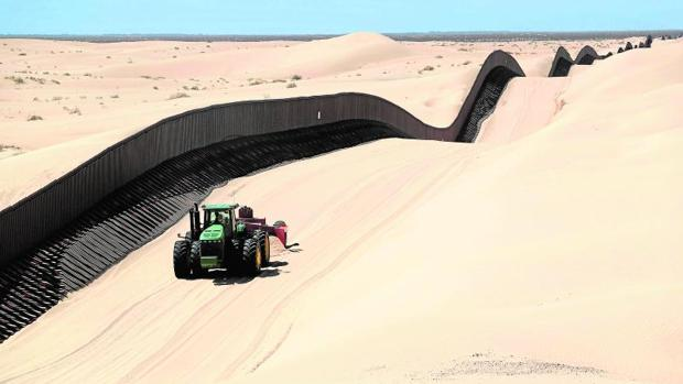 Una máquina quita la arena sobrante en la verja fronteriza con México, en California