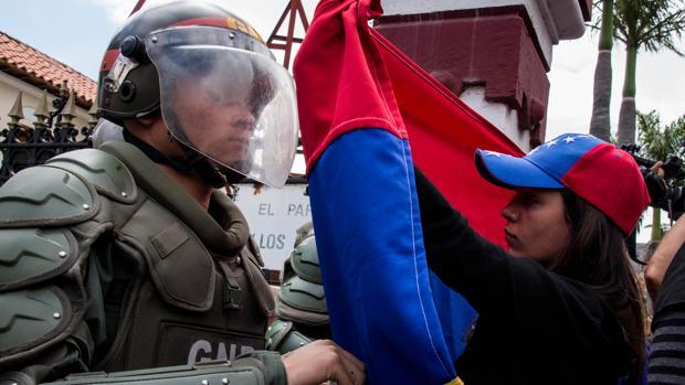 Una mujer sostiene una bandera de Venezuela frente a integrantes de la Guardia Nacional Bolivariana (GNB)