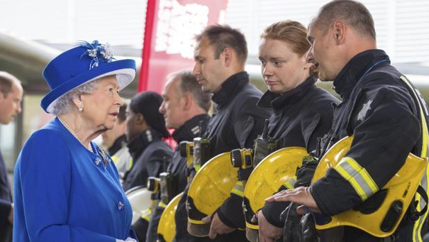 La reina Isabel II conversa con bomberos durante una reunión con residentes de la torre Grenfell en Londres (Reino Unido) hoy, 16 de junio de 2017