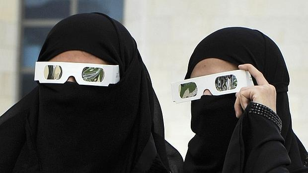 Dos mujeres saudíes observan un eclipse solar parcial en el Mar Rojo