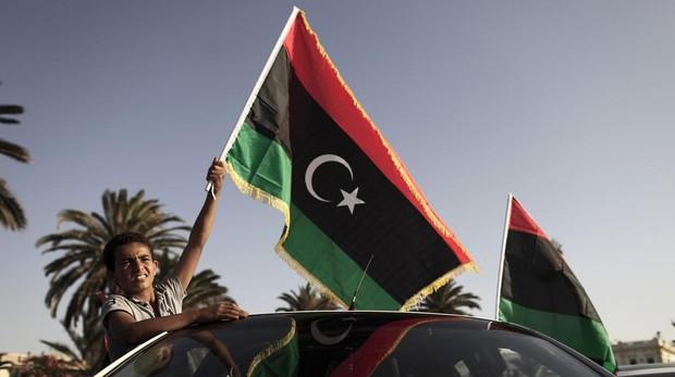 Un joven portando la bandera de Libia en Trípoli