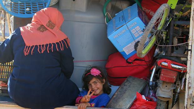 Una niña siria sonríe desde un camión en un puesto de control en Líbano