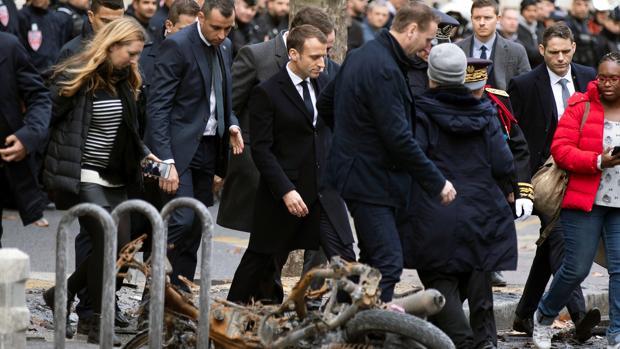El presidente francés, Emmanuel macron (c), pasa junto a una motocicleta calcinada mientras comprueba personalmente los daños materiales ocasionados en las protestas de los llamados «chalecos amarillos»