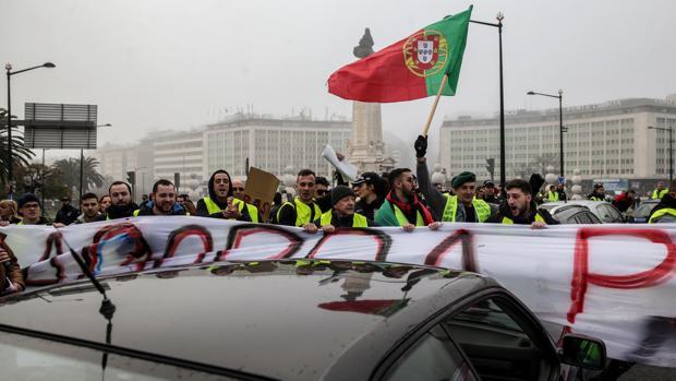 """Manifestantes del movimiento """"chalecos amarillos"""" sostienen pancartas y banderas nacionales durante una protesta en Braga"""