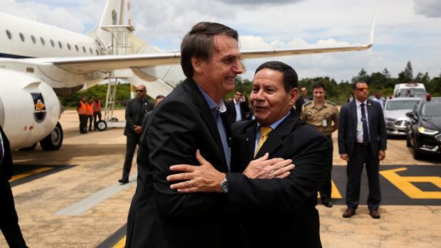 Bolsonaro y el vicepresidente se saludan a su bajada del avión en Brasilia