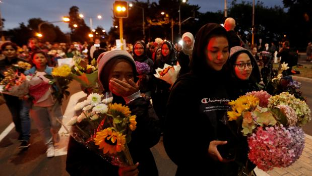 Un grupo de personas con flores avanza tras retirarse un cordón policial frente a la mezquita Al Noor