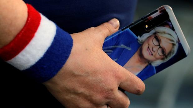 Una seguidora de Le Pen, con su imagen en el móvil durante un acto en Henin-Beaumont
