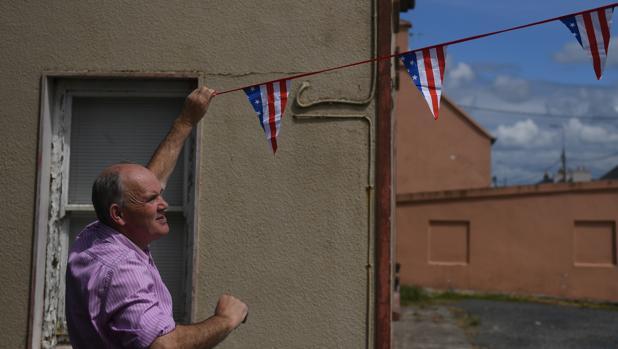 Un hombre coloca banderines con los colores de Estados Unidos en Doonbeg (Irlanda)