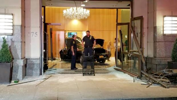 Oficiales de policía parados cerca del coche que se ha estrellado esta pasada noche contra el vestíbulo del «Trump Plaza» en New Rochelle