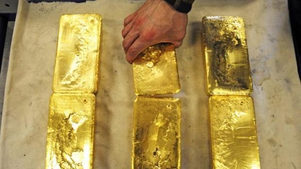 Un hombre coge un lingote de oro
