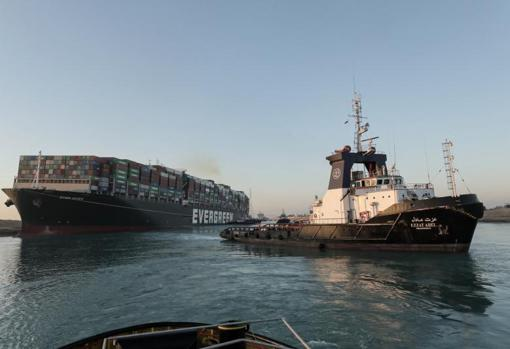 A tugboat tries to move the Ever Given in the Suez Canal rescue operation