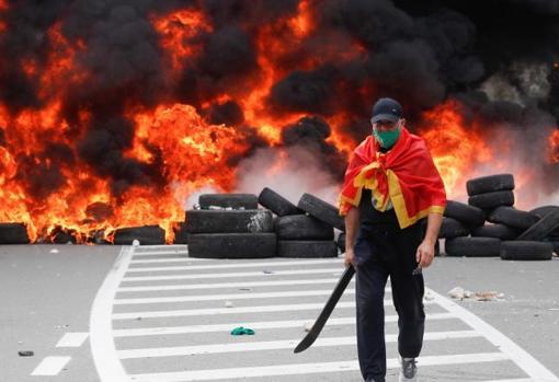 Un manifestante junto a la barricada