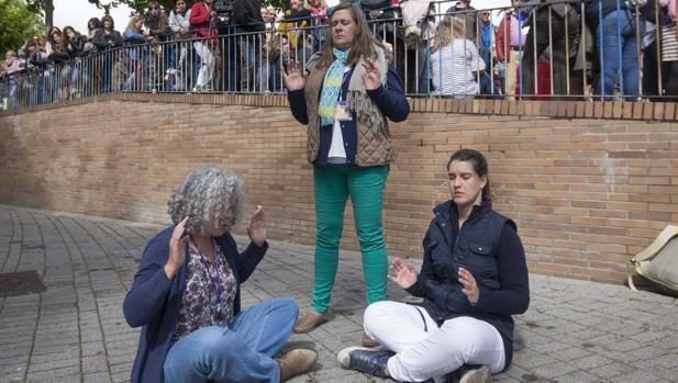 Tres asistentes a «Being one» meditan en los aledaños de la plaza de toros de Leganés