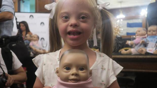 Una niña con síndrome de down sostiene a Oli, el primer muñeco con rasgos de síndrome de Down en Argentina