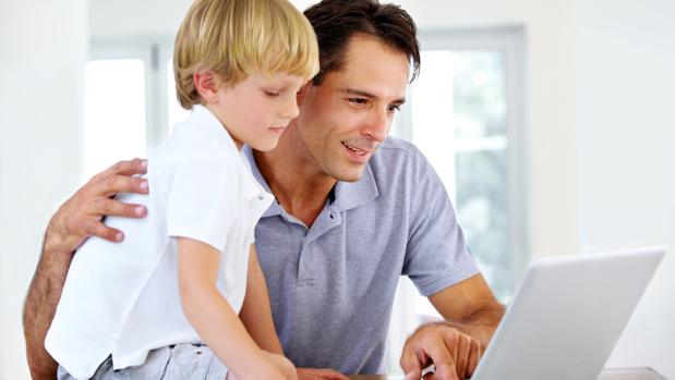 Un hombre consulta internet junto a su hijo