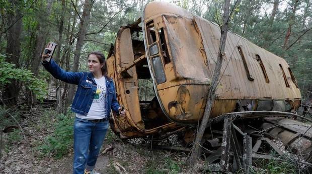Una mujer se fotografía junto a un autobús abandonado durante una visita guiada a Chernóbil