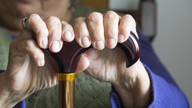 Una anciana se apoya en su bastón
