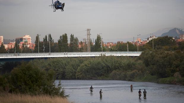 Agentes de los Mossos d'Escuadra y de los Bomberos trabajan en un dispositivo de búsqueda, para localizar el cuerpo de un bebé que un menor habría lanzado al río Besos