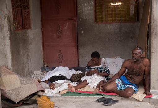 Noel (derecha) y su familia descansan en la entrada de su casa, en Les Cayes (Haití), tras el terremoto registrado el sábado pasado