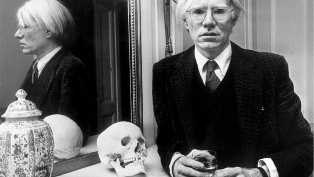 Andy Warhol posa con uno de sus relojes de muñeca
