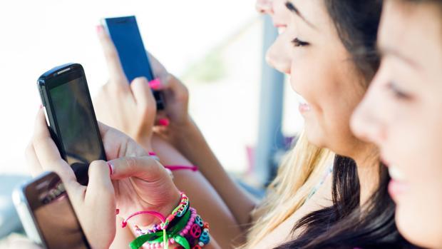 Unos jóvenes utilizan sus terminales móviles para comunicarse a través de internet