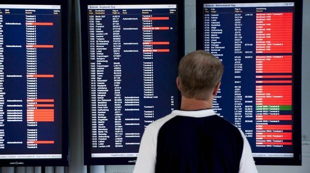 Un pasajero observa el panel deinformación de salidas y llegadas de vuelos en un aeropuerto