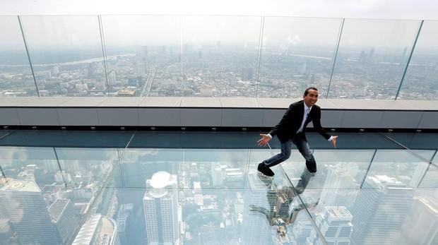 Un ciudadano posa para una foto sobre un suelo de cristal desde el mirador del rascacielos King Power Mahanakhon de Bangkok (Tailandia)